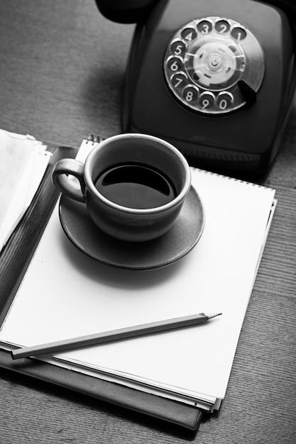 Teléfono retro, cuaderno y taza de café Foto gratis