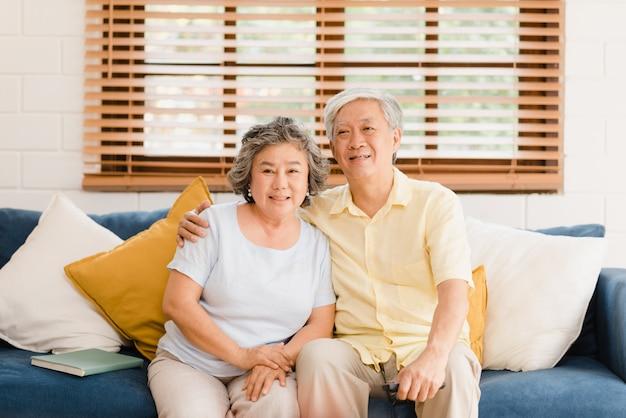 La televisión de observación de los pares mayores asiáticos en la sala de estar en casa, pareja dulce disfruta del momento del amor mientras que miente en el sofá cuando está relajado en casa. Foto gratis