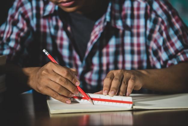 Tema educativo: primer plano escritura del alumno en un aula. Foto gratis