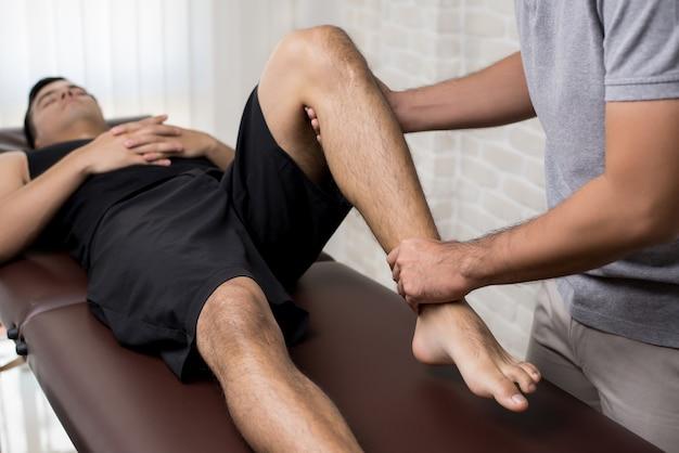 Terapeuta que trata la pierna lesionada del paciente masculino atleta en clínica Foto Premium