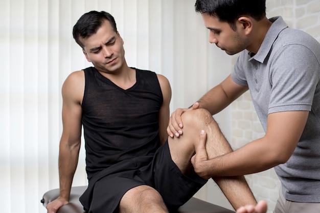 Terapeuta que trata la rodilla lesionada del paciente masculino atleta en clínica Foto Premium