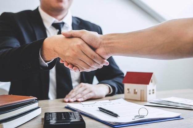 Terminando un acuerdo exitoso de bienes raíces, el corredor y el cliente se dan la mano después de firmar el formulario de solicitud aprobado del contrato, sobre la oferta de préstamo hipotecario y el seguro de la casa Foto Premium