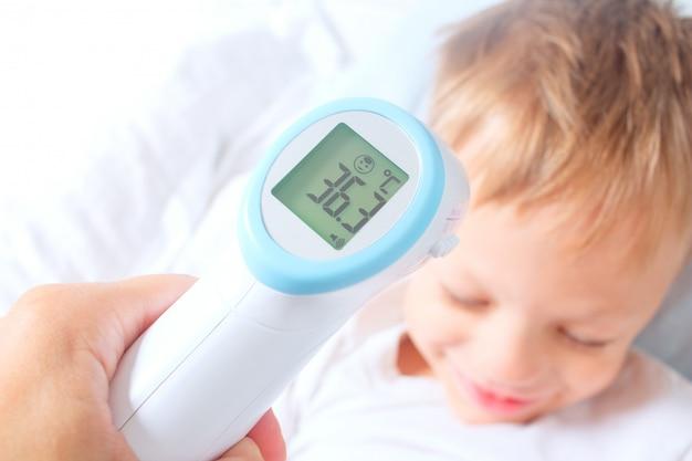 Un termómetro infrarrojo digital sin contacto registró la temperatura corporal normal de un niño. el niño se está recuperando de una enfermedad. prevención exitosa de resfriados y gripe en niños. Foto Premium