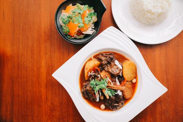 Ternera massaman curry con arroz y ensalada sobre fondo de madera, comida tailandesa Foto Premium