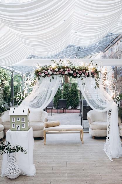 Terraza luminosa de boda al aire libre con arco floral Foto gratis