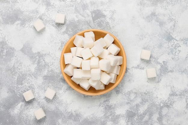 Terrones de azúcar blanco sobre hormigón, vista superior Foto gratis