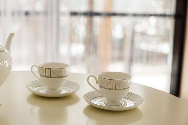 Tetera blanca y dos tazas de té sobre la mesa. Foto Premium