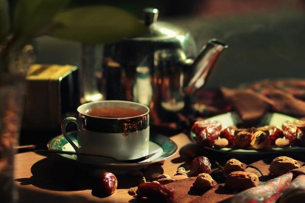 Tetera caliente y taza con dátiles, frutos secos y frutos secos. Foto Premium