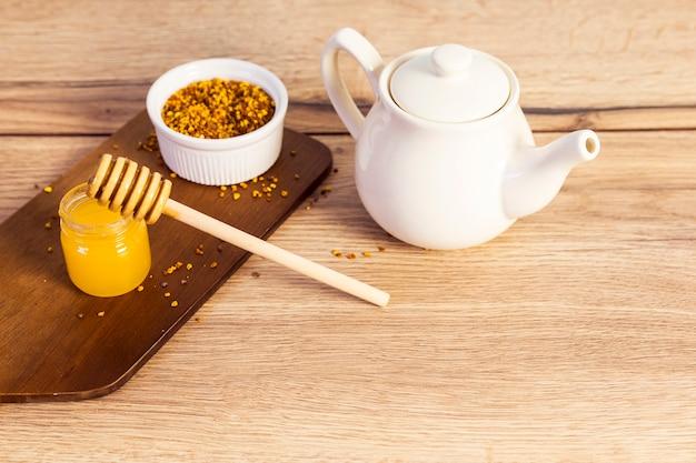Tetera de cerámica con fondo de madera de polen de abeja y miel Foto gratis