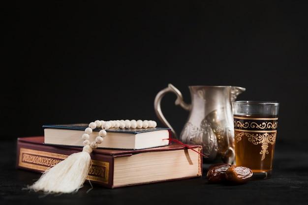Tetera con libro de corán en la mesa Foto gratis