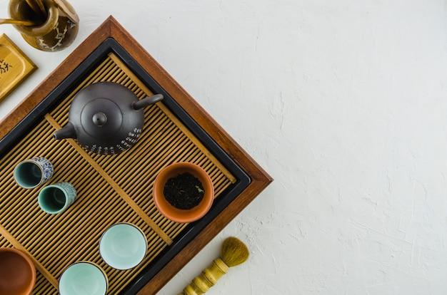 Tetera y tazas de té chinas en el salvamanteles de madera aislado en el fondo blanco Foto gratis