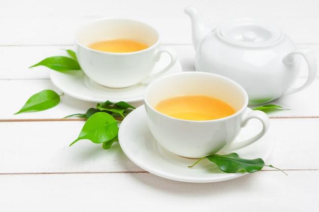 Tetera y tazas de té sobre un fondo blanco de madera Foto Premium