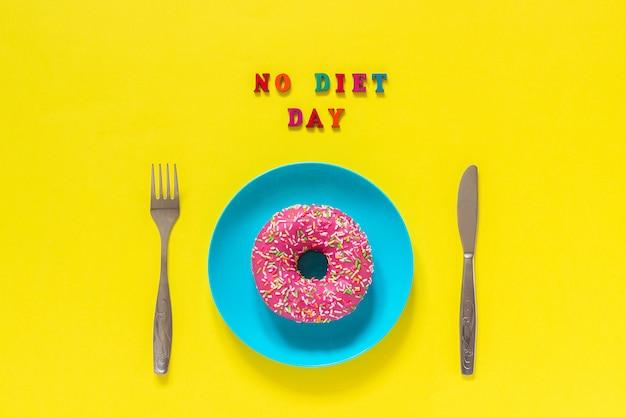 Texto sin día de dieta, rosquilla en el plato y cubiertos tenedor de mesa. Foto Premium