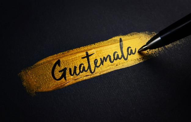 Texto de escritura a mano de guatemala sobre el pincel de pintura dorada Foto Premium
