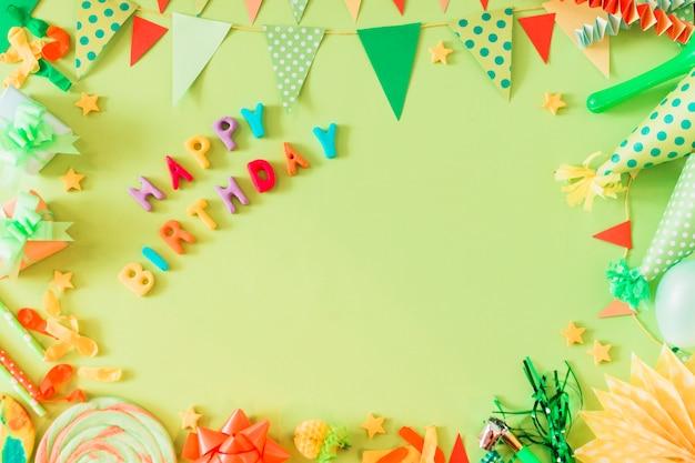 Texto de feliz cumpleaños con accesorios sobre fondo verde Foto gratis