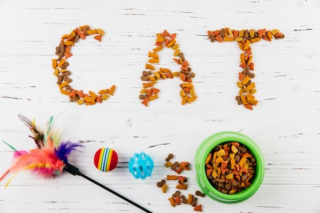 Texto gato de comida para mascotas en superficie de madera blanca Foto gratis