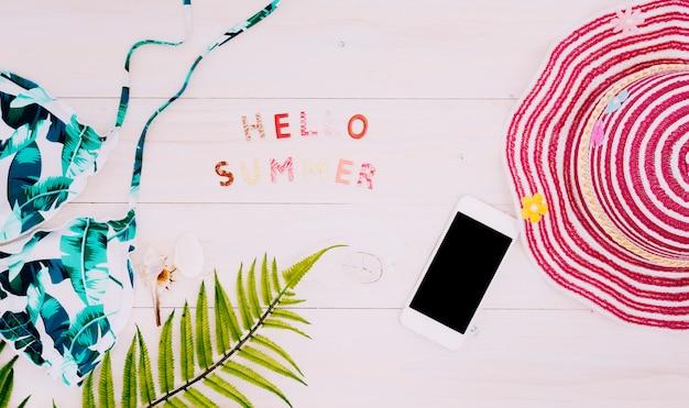 Texto hola verano con cosas de playa en superficie clara. Foto gratis