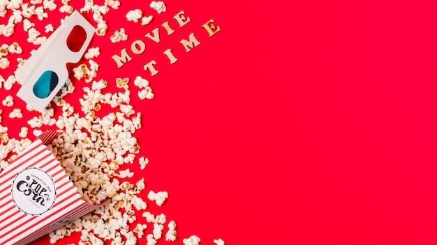 Texto de la hora de la película con gafas 3d y palomitas de maíz derramadas sobre fondo rojo Foto gratis