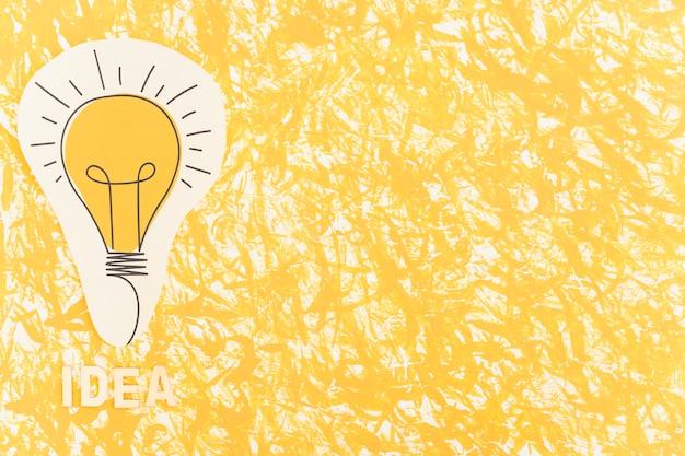 Texto de la idea cerca del papel de la bombilla recortada en el telón de fondo con textura Foto gratis