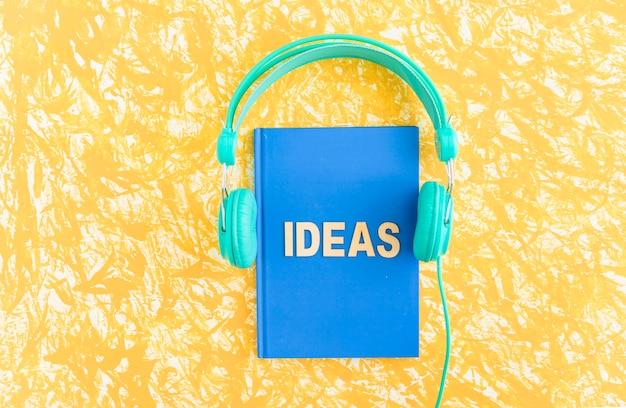 Texto de ideas en el cuaderno de tapa azul con auriculares en el fondo amarillo Foto Premium
