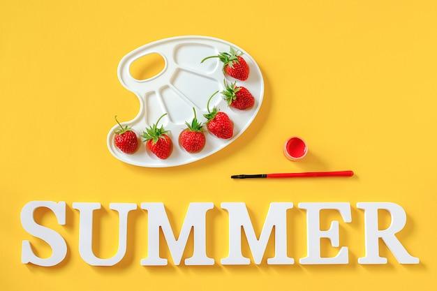 Texto de verano, fresas rojas maduras en una paleta artística, pincel y gouache sobre fondo amarillo Foto Premium
