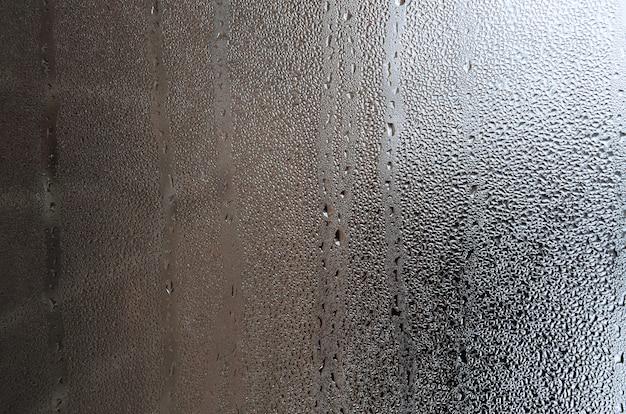 Textura de una gota de la lluvia en un fondo transparente mojado de cristal. tonos en color gris. Foto Premium