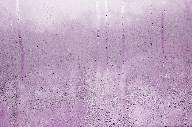 Textura de una gota de la lluvia en un fondo transparente mojado de cristal. tonos en color rosa. Foto Premium