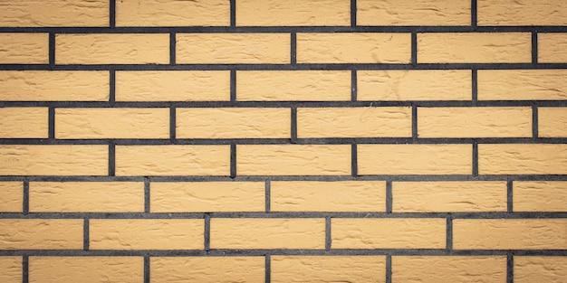 Textura de pared de ladrillo, fondo de piedra. patrón de ladrillos amarillos. panorámica amplia, pancarta panorámica. fachada de arquitectura, superficie de mosaico, marco de roca. Foto Premium