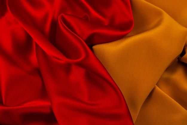 La textura de la tela de lujo de seda o satén roja y naranja se puede utilizar como fondo abstracto. Foto Premium
