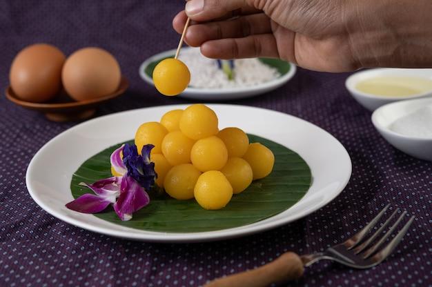 Thong yod postre en una hoja de plátano en un plato blanco con orquídeas y un tenedor Foto gratis