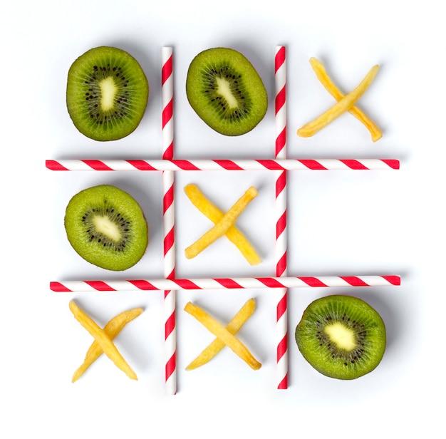 Tic tac plano, plano, hecho de kiwi, papas fritas y pajitas. Foto Premium