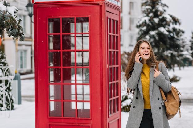 Tiempo de invierno congelado de alegre joven moda caminando en la calle cerca de la cabina de teléfono roja. hablar por teléfono, reír, pasar la nieve, esperar la navidad, expresar alegres emociones positivas. Foto gratis