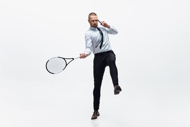 Tiempo de movimiento. hombre en ropa de oficina juega tenis aislado en blanco. empresario formación en movimiento, acción. aspecto inusual para deportista, nueva actividad. deporte, estilo de vida saludable. Foto gratis