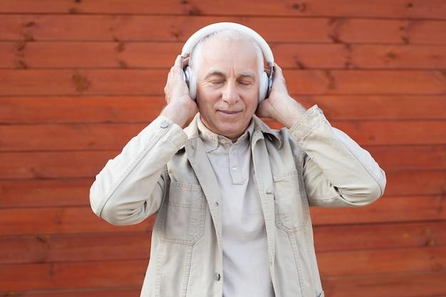 Tiempo de música relajante. retrato de hombre senior en auriculares escuchando música manteniendo los ojos cerrados mientras está de pie contra el fondo de pared de madera Foto Premium