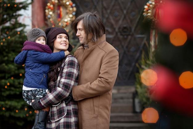 Tiempo de navidad. feliz madre de familia, padre y niña caminando en la ciudad y divertirse. viajes, turismo, vacaciones y personas. varsovia, polonia Foto Premium