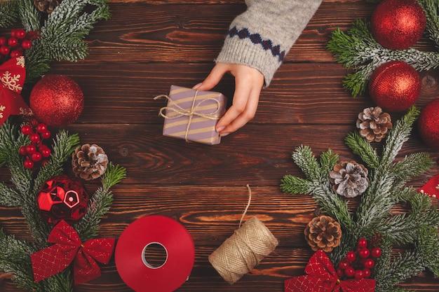 Tiempo de navidad. proceso de embalaje de regalos para vacaciones Foto Premium