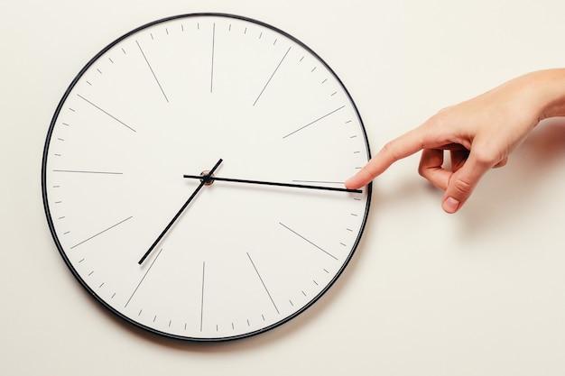 Tiempo de parada de mano de mujer en un reloj redondo, gestión del tiempo y concepto de fecha límite Foto Premium