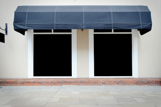 Tienda frente de tienda vintage con toldos de lona y pantalla en blanco Foto Premium