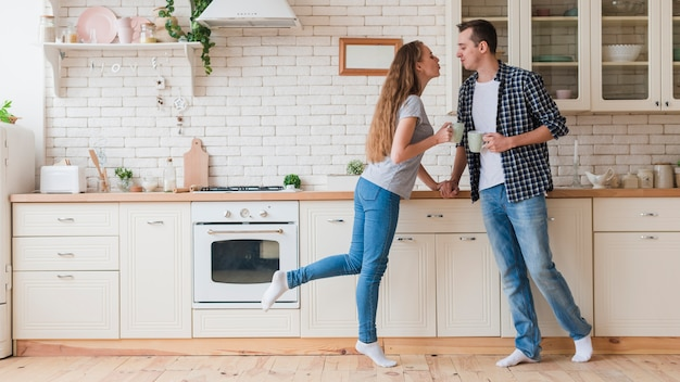 Tierna pareja bebiendo té y de pie en la cocina Foto gratis