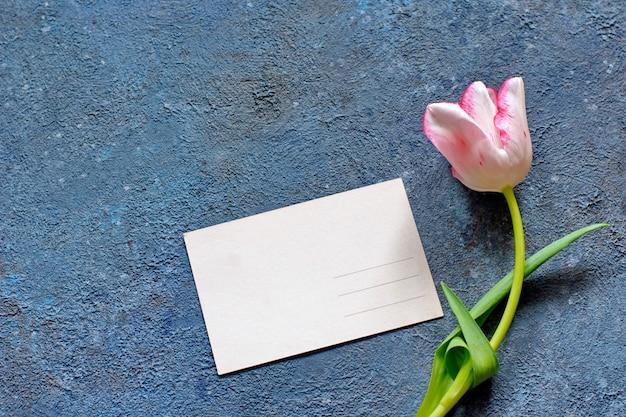 Tierna primavera tulipán y una tarjeta postal en cemento gris Foto Premium