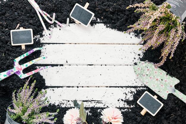 Tierra negra planta en maceta; flores; pizarra en blanco; y herramientas de jardinería sobre escritorio de madera. Foto gratis