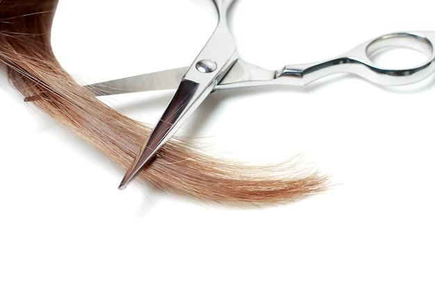 Tijeras y cabello castaño aislado sobre fondo blanco. Foto Premium
