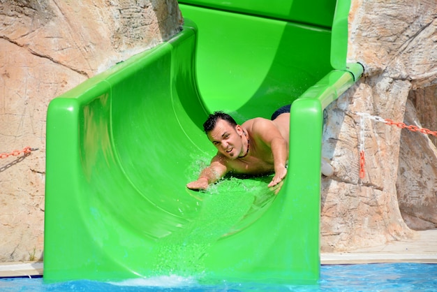 Tío en tobogán de agua durante las vacaciones de verano Foto gratis