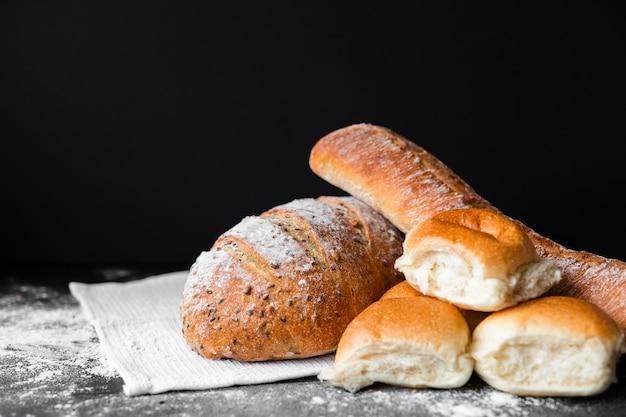 Tipos de pan fresco con harina sobre tela Foto gratis