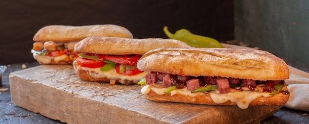 Tipos de sándwich mixto con varios alimentos en una tabla de madera Foto gratis
