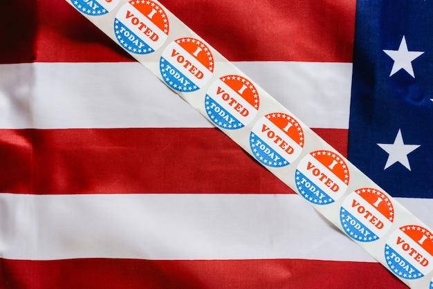Tira de adhesivos voto hoy en la bandera de los estados unidos después de votar en la urna. Foto Premium