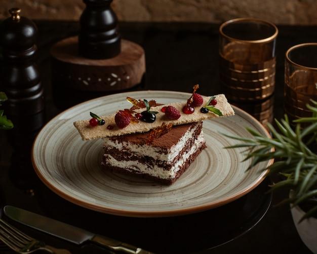 Tiramisú de cacao con galleta dulce y bayas del bosque en la parte superior Foto gratis
