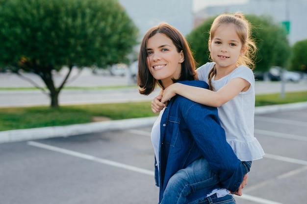 Tiro al aire libre de la mujer sonriente da a cuestas a su hija, tienen caminar al aire libre Foto Premium