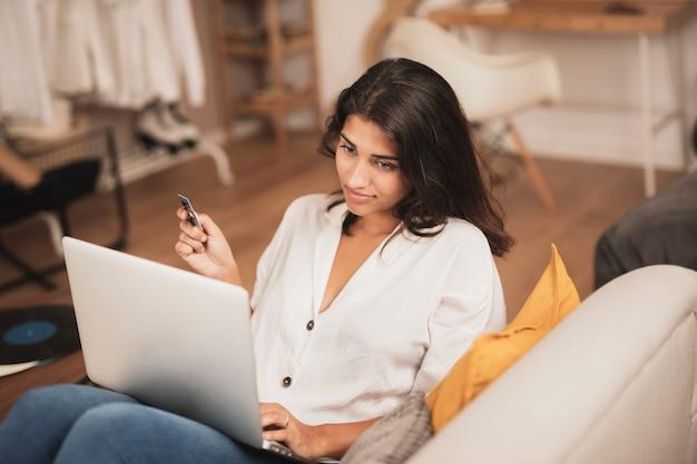 Tiro de alta vista de mujer sosteniendo una tarjeta de crédito y usando su laptop Foto gratis