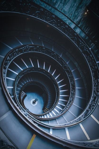 Tiro de ángulo alto de escaleras de caracol negro en un museo en el vaticano Foto gratis